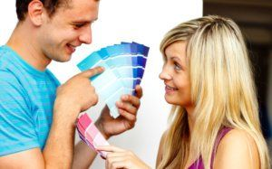 Cute couple chosing colors for painting house